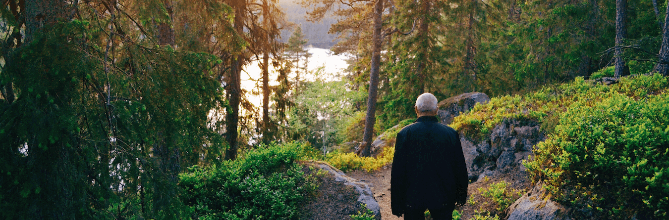 elderly man walking on a wooded path