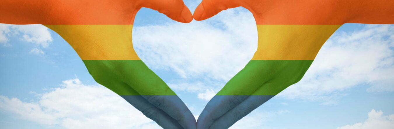 Hands painted as the rainbow flag forming a heart, symbolizing gay love on blue sky.