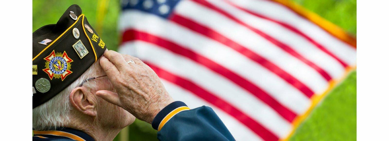 Senior veteran saluting American flag